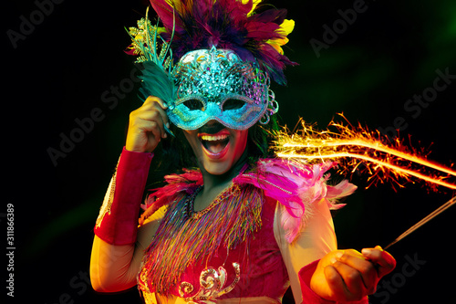 Foto Beautiful young woman in carnival mask and stylish masquerade costume with feathers and sparklers in colorful lights on black background