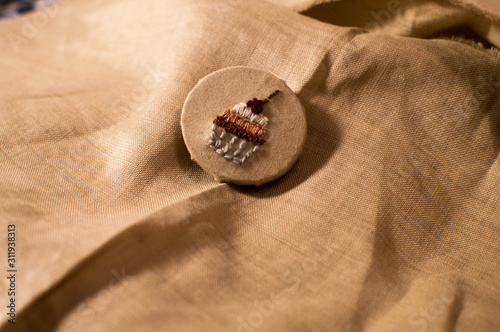 Foto Homemade brooch made from linen with cupcake symbol
