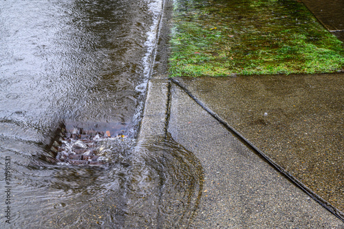 Fotografie, Tablou Heavy rain caused flooding in street, water swirling around storm drain