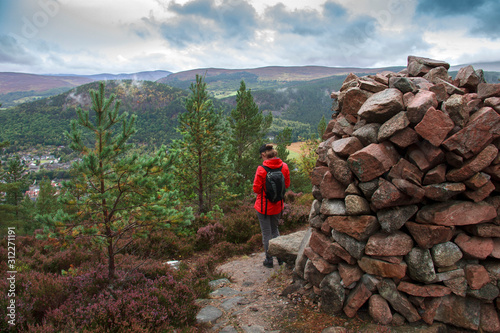 Fotografiet Female tourist stands on the top of Craig Coillich with view at Ballater below