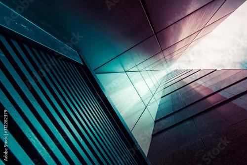 Fototapeta premium Abstrakcyjne tło. Zobacz przez nowoczesny komin wysokiego wieżowca w górę do błękitnego nieba z białymi chmurami - abstrakcyjne tło szczegółów architektury w turkusowych turkusowo-niebiesko-fioletowych kolorach