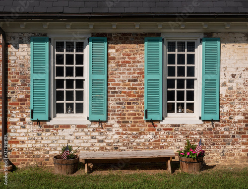 Canvas Print Simple blue shutters around white windows against a brick wall in colonial house
