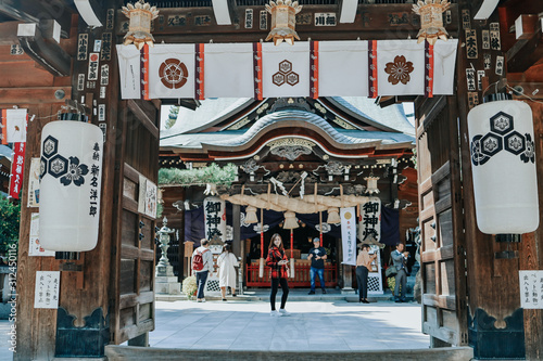 Girl in red suit in front of Kushida Shrine is a Shinto shrine located in Hakata-ku, Fukuoka, Japan Fototapeta