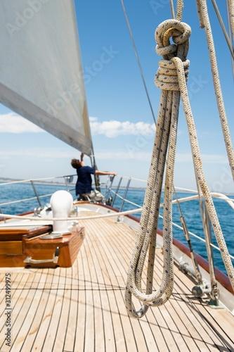 Stampa su Tela Man working on prow of yacht