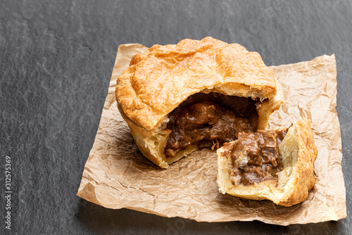 Puff pastry steak pie on baking paper on black stone backgroung