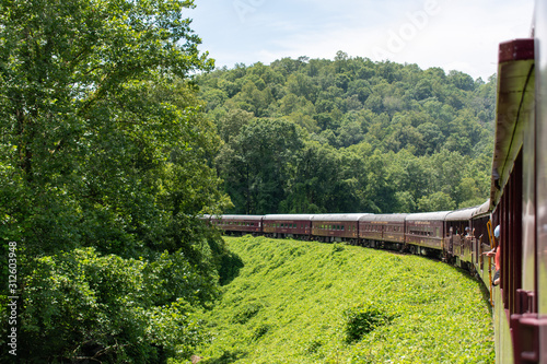Photo A horizontal, landscape orientation of a train making a big turn through the mountains and rural countryside of North Carolina