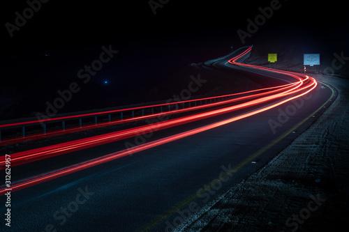 Fototapeta highway long exposure vehicle light trails curvy highway between mountains eilat