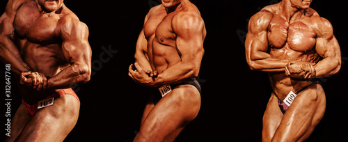 Foto group athletes bodybuilders posing biceps on hand in bodybuilding competition on