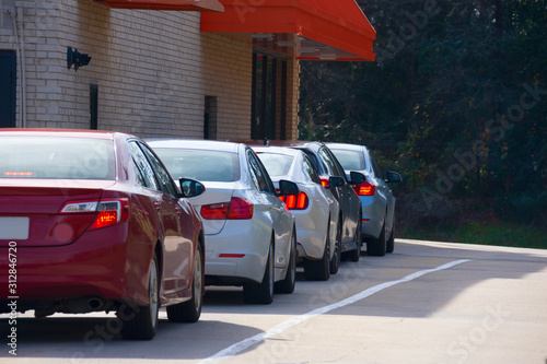 Photo Generic drive thru pickup window with cars waiting in line to get their products