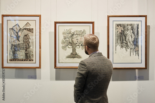 Obraz na plátně Rear view of young man in suit looking at modern art on the wall in museum