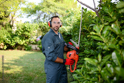 Obraz na płótnie handsome young man gardener trimming hedgerow in a garden park outdoor
