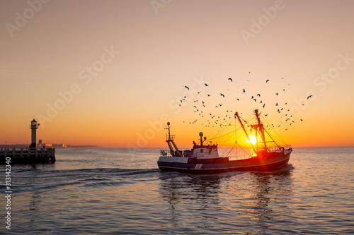 Fishing boat in front of the old wooden pier of Nieuwpoort (Belgium) at sunset Fototapeta
