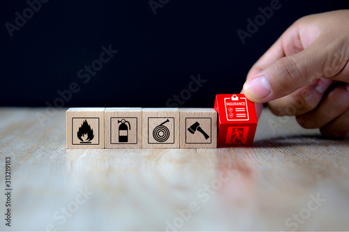 Close-up hand choose a red wooden toy blocks with insurance policy icon for fire safety protection concepts Fototapeta
