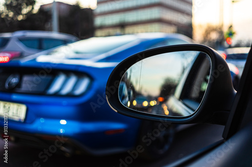 Платно Traffic seen thru a car mirror and a Mustang in the background at sunset in Buch