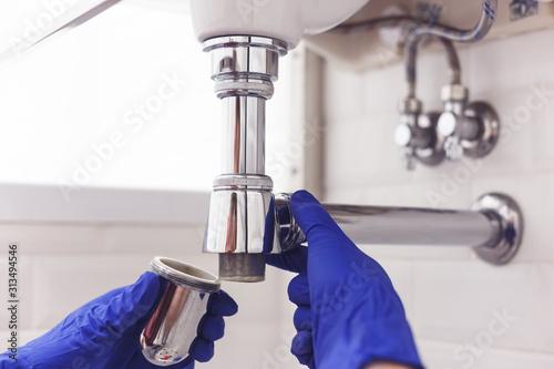 Fotografija Plumber repairs and maintains chrome siphon under the washbasin