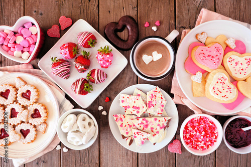 Valentines Day table scene of assorted sweets and cookies. Top view over a rustic wood background. Love and hearts theme.