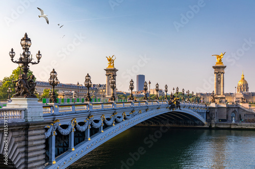 Pont Alexandre III bridge over river Seine in the sunny summer morning. Bridge decorated with ornate Art Nouveau lamps and sculptures. The Alexander III Bridge across Seine river in Paris, France.