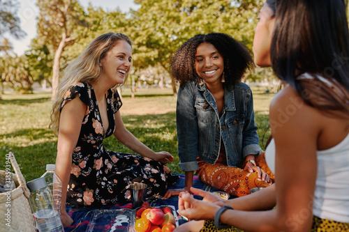 Fotografia Group of smiling multiracial female best friends sitting together on blanket wit