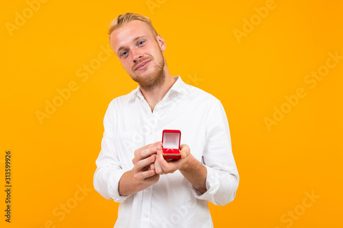 Fotografia, Obraz young man in a white shirt makes a marriage proposal to a girl holding a ring on