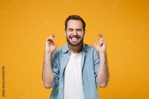 Fotografia Young bearded man in blue shirt posing isolated on yellow orange background
