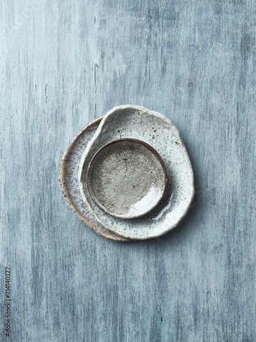Hand crafted blue and gray ceramic plates on painted wooden background Fotobehang