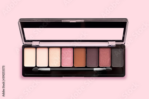 Carta da parati Palette of eyeshadows in brown tones, matte and shimmer eyeshadows on a pink background, top view