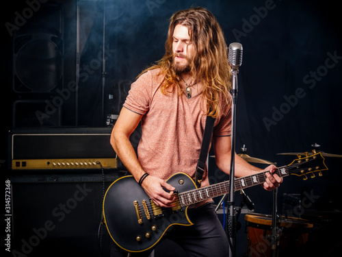 Fototapeta Young man playing electric guitar on stage