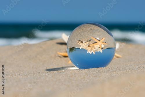 Lensball summer vacation landscape with starfish reflection Fototapeta