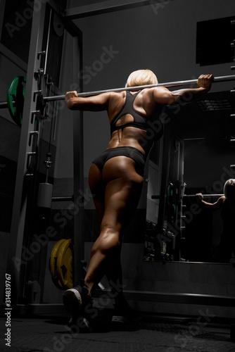 Leinwand Poster Woman training on smith machine.