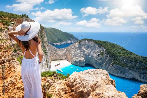 Fototapeta Eine Touristin in weißem Kleid steht auf einer Klippe und genießt die Aussicht a