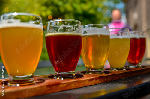 Photo Craft beer tasting: five glasses with beers of different colors and flavors