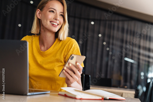 Photo of smiling blonde woman using laptop and smartphone while sitting Fototapeta