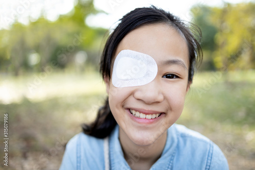 Fotografia Happy asian child girl cover with blindfolded bandaged eye after surgery or trea