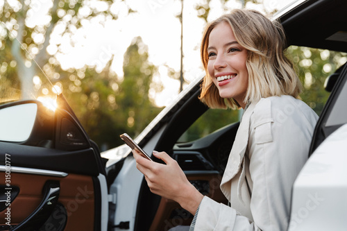 Stampa su Tela Image of beautiful businesslike woman sitting in car and using cellphone