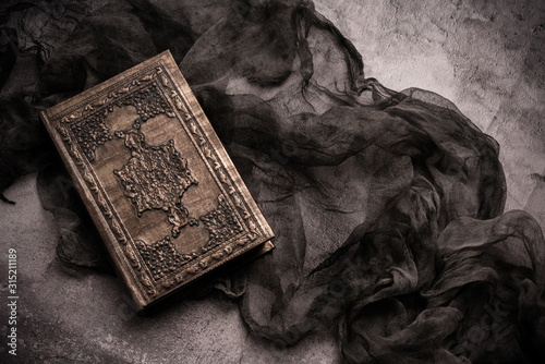 Wallpaper Mural Old book with spells and magic wand on gray background with witch rag