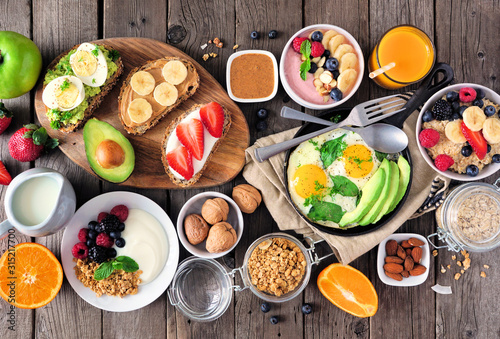 Healthy breakfast table scene with fruit, yogurts, oatmeal, smoothie, nutritious toasts and egg skillet Fototapet