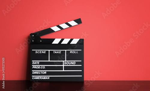 Fotografia Blank Film clapper board or movie clapper cinema board , Slate film on black wooden with red wall background