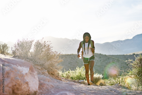 Fotografie, Tablou woman hiking at Red Rock Canyon during sunset with backpack