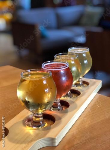 Fotografia, Obraz Flight of Beer and cider served on a wooden paddle