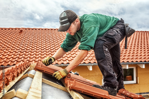 Fotografia Roofer at work, installing clay roof tiles, Germany