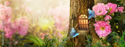 Zaczarowany bajkowy las z magicznym lśniącym oknem w zagłębieniu domu elfów z drzewa sosnowego, kwitnący bajeczny olbrzymi różowy ogród różanych kwiatów, latający magiczny niebieski paw oko motyl, miejsce