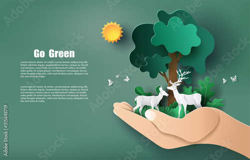 Obraz na płótnie Paper art style of hand holding tree and plants with deers, save the planet and energy concept