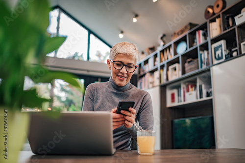 Smiling trendy senior woman using smart phone in home office, portrait.