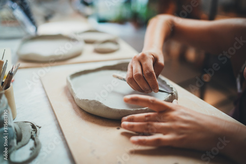 Foto Closeup Image of Female Hands Works with Clay Makes Future Ceramic Plate, Profes