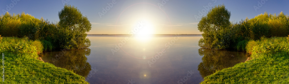 Beautiful view of lake with shore overgrown with reeds in sunny day. Rest in nature. Panoramic banner. Landscape on sunrise.