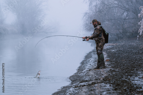 Fisher man fishing with spinning rod on a river bank at misty foggy winter, spin Fototapete