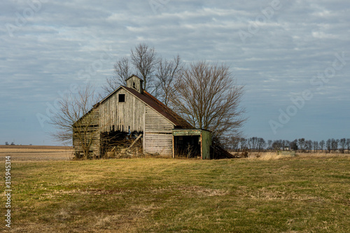 Fototapeta An abandoned corn crib or barn with a lean to on the side