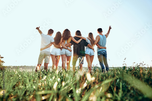 Canvas Print A group of people huddle in a field.