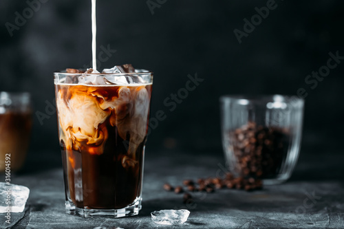 Photographie Milk Being Poured Into Iced Coffee on a dark table
