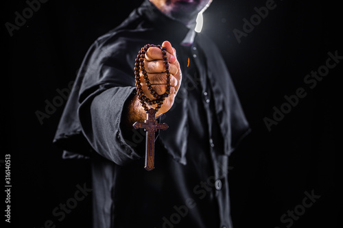 Fotografia, Obraz The priest holds the cross on black background For Halloween concepts